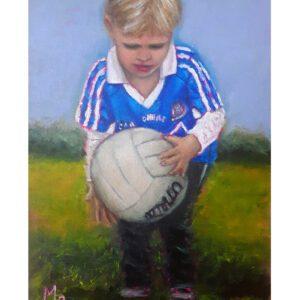 Blonde boy holding football dublin GAA colours