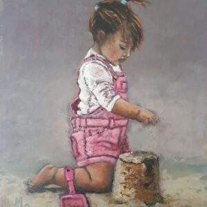 Little girl pink dungarees and pigtails making sandcastle
