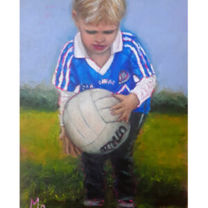 Boy in Dublin GAA jersey holding a football