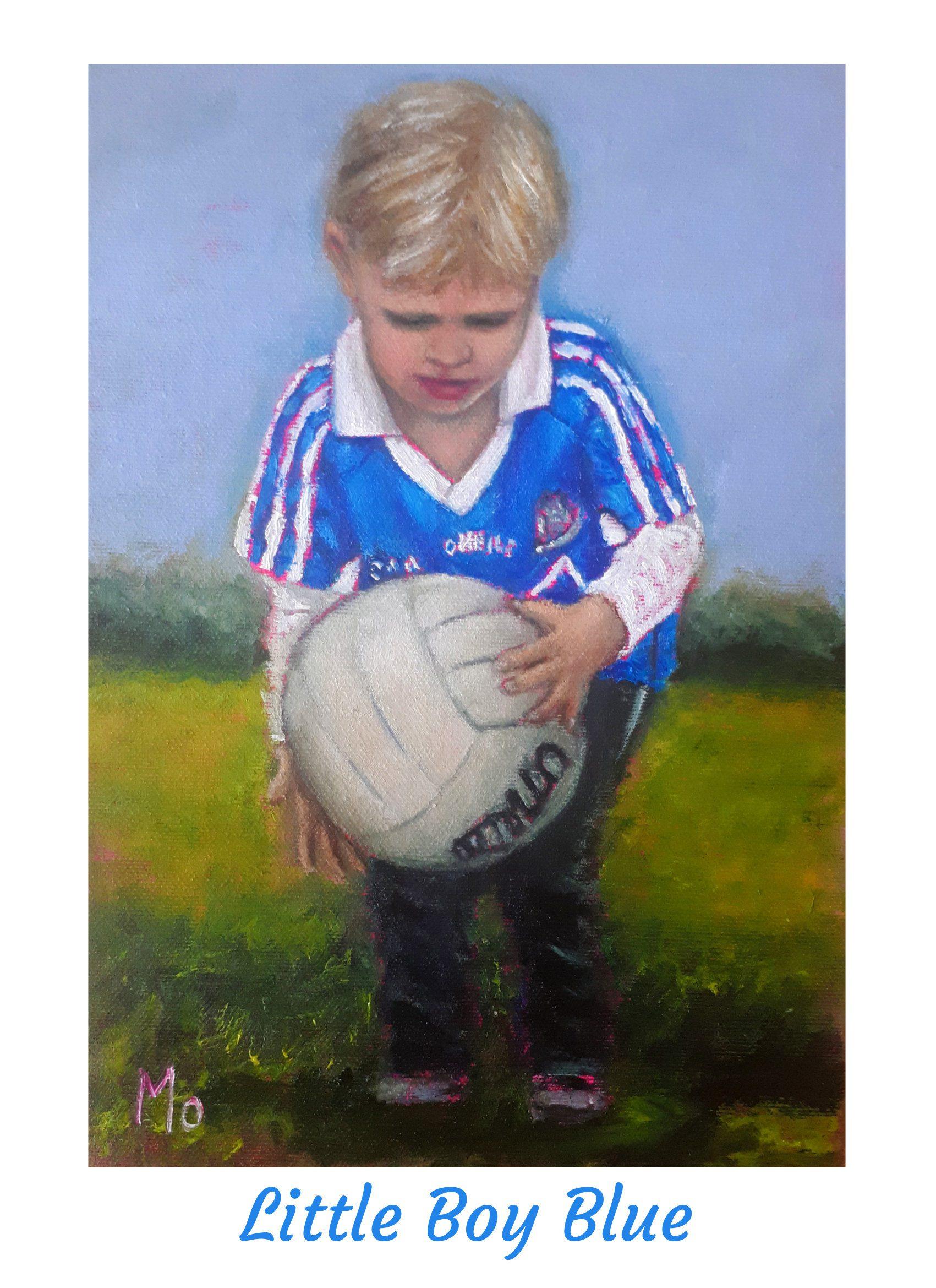 Boy in Dublin GAA jersey holding a football