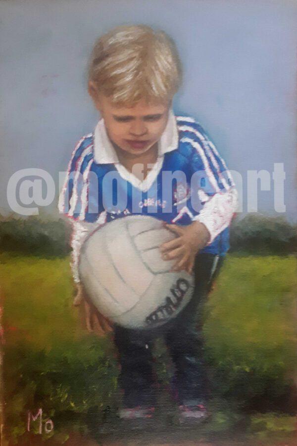 Little blonde boy Dublin GAA jersey about to kink a ball