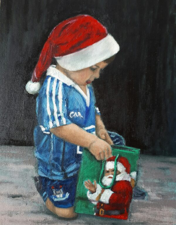 Little boy Santa hat and Dublin jersey looking into a christmas bag