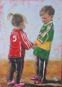 Little boy and girl Cork and Kerry GAA jerseys holding hands