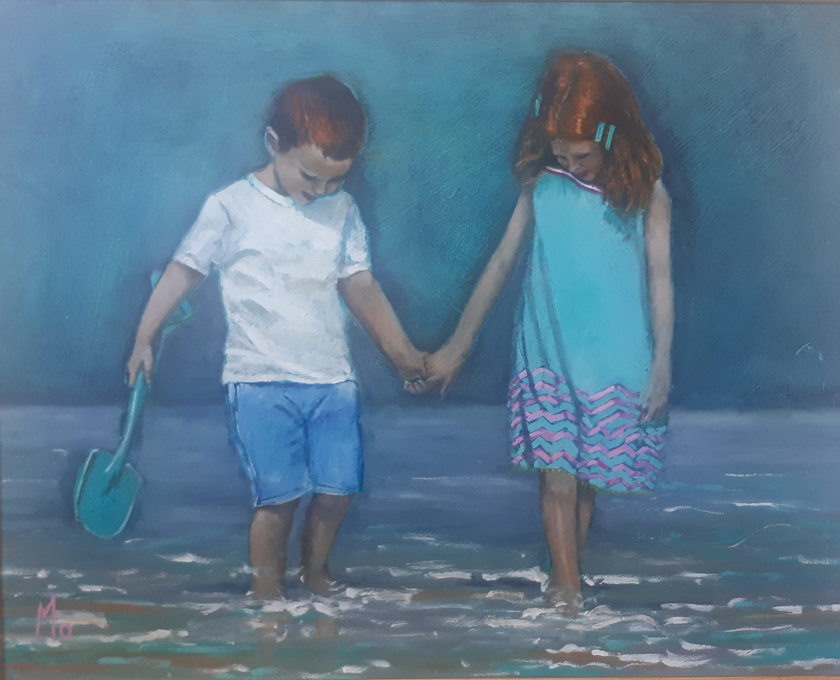 Two little redheads on the beach holding hands