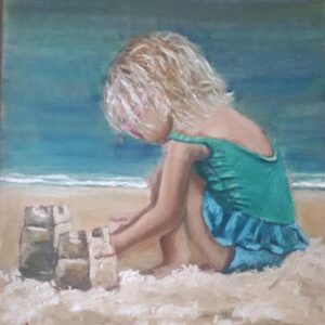 Little girl wearing sunglasses building sandcastles