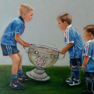 Three boys in Dublin Jerseys lifting the Sam Maguire