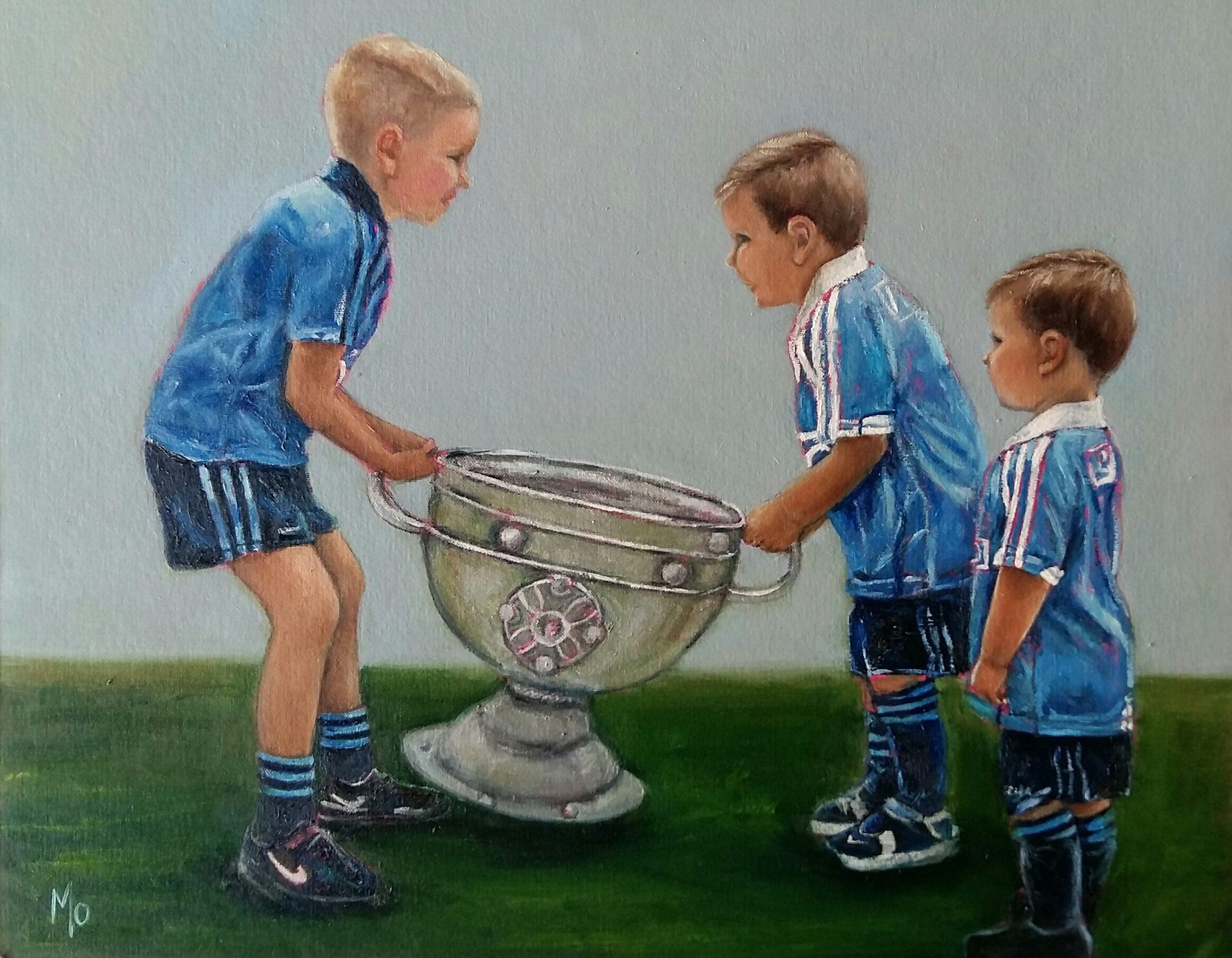 Three boys in Dublin Jerseys lifting the Sam Maguire