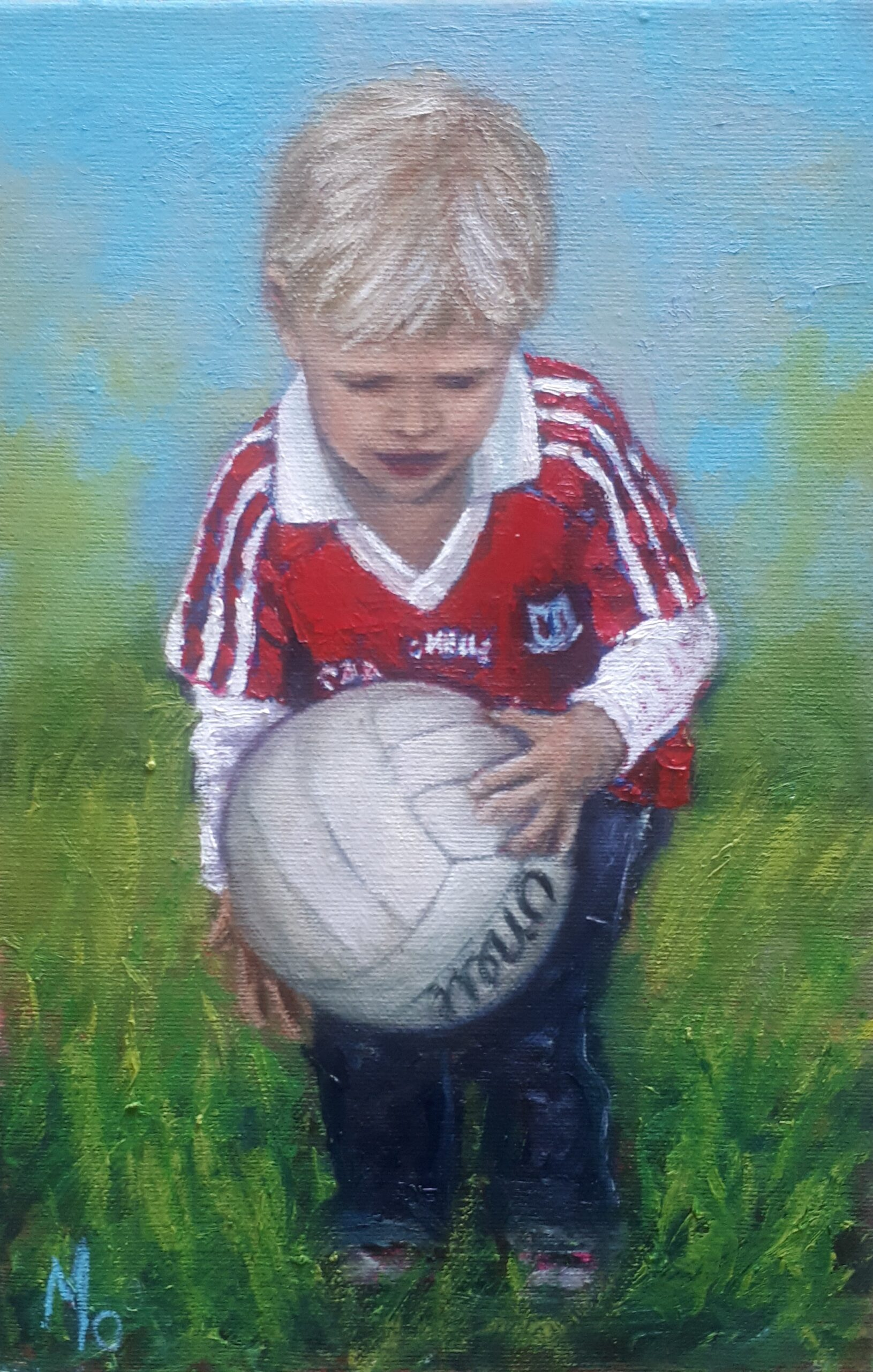 young boy with red jersey with football