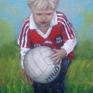 Boy in Cork GAA jersey holding a football