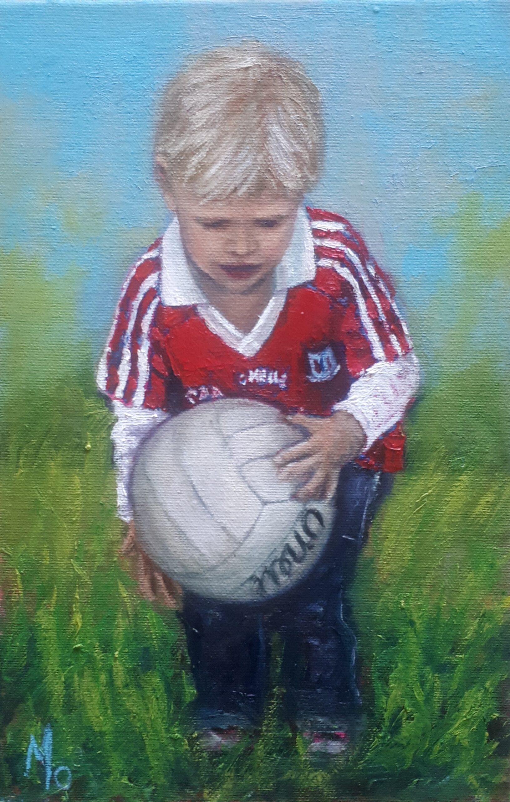 Little boy in cork GAA jersey holding a football