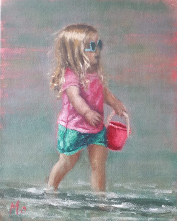 girl on beach with pink bucket